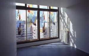 Blick vom Inneren einer Wohnung nach außen, Fassadendetails auf der Fensterscheibe
